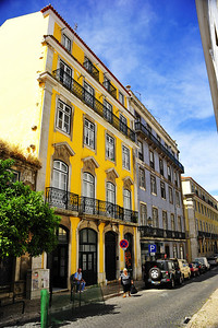 Alfama section of Lisbon has buildings decorated with ceramic tiles and bright colors