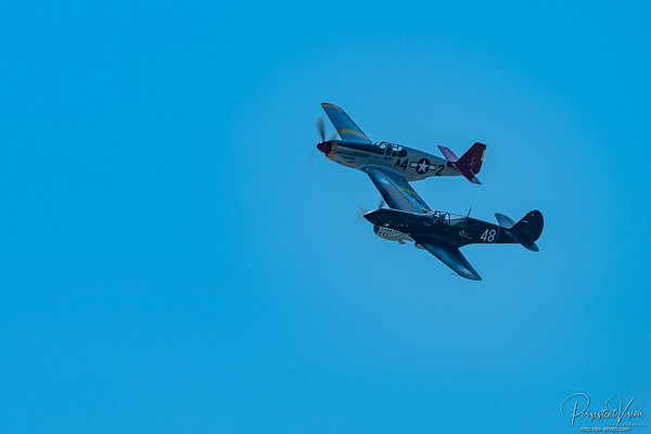 """The Commemorative Air Force (CAF) Red Tail Squadron's P-51C Mustang, named Tuskegee Airmen, is an authentic and fully restored operational fighter from the WWII era. This awe-inspiring aircraft sparks conversations to educate young and old alike about the often-overlooked history of the Tuskegee Airmen that flew this same model as their signature aircraft in WWII. It is quite simply a museum without walls… and an awe-inspiring one at that!  Our P-51C Mustang Tuskegee Airmen, tail number N61429, saw service stateside as a trainer in 1945, then declared surplus after the war ended. It was displayed at Montana State College (now Montana State University) for 40 years before being donated for restoration. The CAF took possession of the aircraft in the late 1980s, and was initially restored to flying condition in 2001. --------------------------------------------------------- This P-40 Warhawk has seen some incredible action and still flies to tell about it!  Sam Graves pilots the Commemorative Air Force P40 Warhawk, which is painted in the period correct colors of the Famous AVG Flying Tiger WWII Ace David Lee """"Tex"""" Hill."""