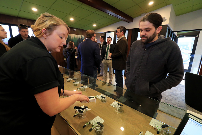 The area's first pot dispensary Sanctuary Medicinals in Gardner held its official ribbon cutting on January 4, 2019. Customers were still buying products during the event. The shops Patient Care Advisor Liz Hinde helps customer Brendan Belliveau of Fitchburg with his needs. SENTINEL & ENTERPRISE/JOHN LOVE