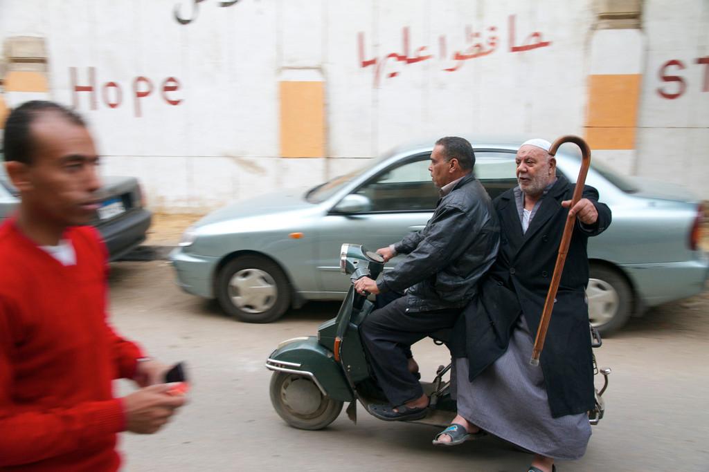 """...<br /> REVOLUCIJA<br /> <br />    Kairo tiste dni ni bil ravno brezbrižno zatočišče za urejanje novega potnega lista, sudanske vize in nekaj dovoljenj povezanih z državami, ki so bile na najinem seznamu proti jugu kontinenta. <br />    Kolonialne hiše mogočnega mesta ob Nilu so jasno izražale, da je tam nekoč bivalo prestižno življenje na Orientu. Okrogli kovani balkončki, visoka zaobljena okna, mogočni stebri, gravure, čutno izrezljani oboki ... so bili brez najmanjšega dvoma dota Evrope. A so se njeni dediči, ki so zamenjali nekoč sofisticirano meščanstvo, vrnili na nivo srednjega veka in gojili odnos do zapuščine kot do ničvredne ropotije. Polomljene šipe, zbledele odluščene fasade s hlevi na vrhu stavb so se sramovale sredi umazanije in splošne zanemarjenosti, skozi katero smo se med smrdljivim prometnim neredom neorganizirano premikali ljudje. Pred vhodi v stanovanjske hiše so gnili odpadki, ki jih nihče ni odpeljal in so se kopičili v katastrofalnih dimenzijah. K sreči je v mestu živelo še nekaj očarljivosti. Melanholija z mamljivim vonjem po kardamomu in jabolčni sapi je prihajala iz čajnic, kjer so žvenketali kozarčki in je skozi njihova okna puhal dim po tobaku. Tradicionalnost se je srečevala z modernostjo prav tako, kot so šli skupaj vodna pipa, nogomet in novice s Tahrirja.   <br />    """"Nocoj grem na demonstracije,"""" se je zaupal študent Tarik, ki nama je pomagal z začetnimi koraki arabščine. """"Čutim, da moram biti tudi jaz zraven,"""" je bil prepričan mladi Egipčan zelo temne polti, črnih oči in košatih fedrastih las. """"Revolucija zadeva Egipt, torej tudi mene,"""" ni razmišljal nič manj energično, kot je iz zvočnikov pela Umm Kulthum in se je njen močan glas prepletal z melodijo darbuke."""