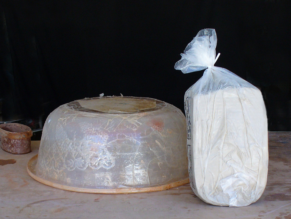 Your pot starts as a slab cut from a block of clay (shown wrapped in plastic). We pick a form that will give us the size pot we want.  Containers take on a new perspective when you build pottery....you look at them as potential molds rather than containers...!