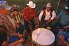 Enfant se bouchant les oreilles près d'un tambour battu par les anciens durant un pow-wow. Réserve crow/Etat du Montana/USA