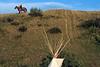 Cavalier portant un drapeau américain sur une colline dominant un site de pow-wow. Réserve crow/Etat du Montana/USA