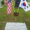 The U.S. and South Korea flags and a carnation adorn the grave marker of a Korean War veteran.
