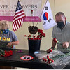 Michelle Silveira of Pelham, N.H., executive director of Power of Flowers, and Dracut Veterans Services Officer Jeffrey Hollett prepare the carnations.