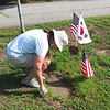 A volunteer prepares to place a headstone on a grave marker.