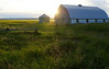 Barn and bin silhouetted by the seting sun