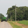 John Deer combine on country road next to Spoon River single phase power line