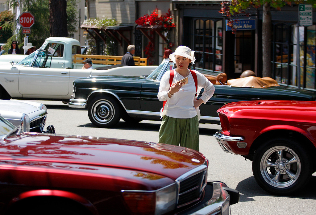 . Jia Wang from China looks at the classic cars at the Prancing Ponies All Women Car Show in Carmel on Wednesday, Aug. 16, 2017.   (Vern Fisher - Monterey Herald)