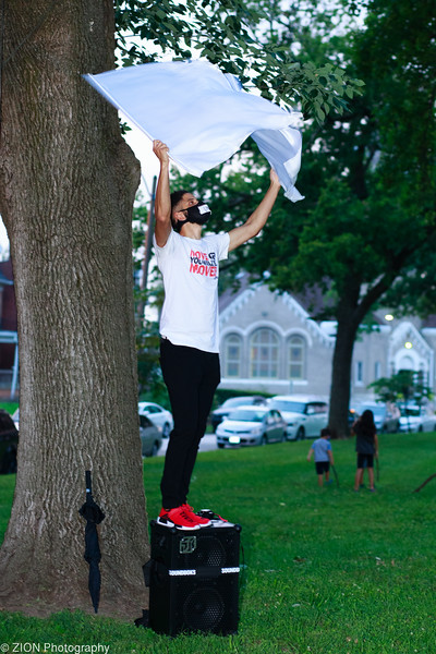 A man artistically flies white flags in the park