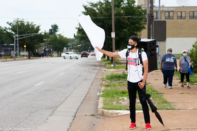 A man stands flying a white flag during pray on MLK