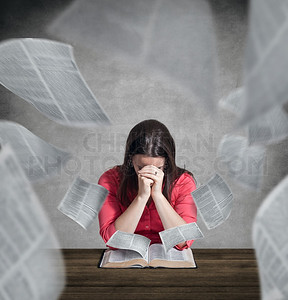 Woman praying with pages flying