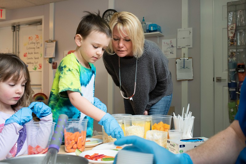 KELLY FLETCHER, REFORMER CORRESPONDENT -- Martha Missale, owner of Miss Martha's Creative Early Learning Program, watches one of her Pre-K students plate up vegetables that will be served with the lunch they are helping to make with Chef Chris Parker, Food Service Director at Windham Central Supervisory Union.  The goal of Chef Chris's visit was to talk about healthy foods and to get kids used to seeing a sample of the meals they'll be eating when they move up to Kindergarten in the Fall.
