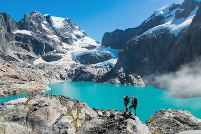 Two mountaineers standing above Donne Glacier Lake and opposite Donne Face and Glacier of Mount Tutoko, Darran Mountains, Fiordland National Park, New Zealand