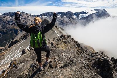 Female walker (20's) raises arms in front of mount Rolleston. Avalanche Peak, Arthur's Pass