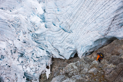 Climber descending into Donne Valley beneath Taoka Icefall, Darran Mountains, Fiordland