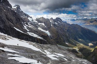 Climber descends rock slabs above Cleft Creek, Northern Darran Mountains, Fiordland National Park