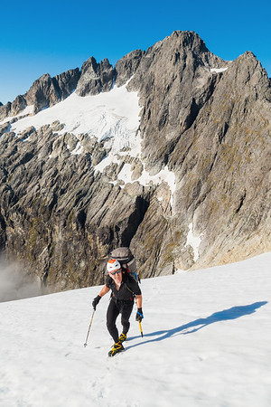 Mountaineer crosses snowfield below Waitiri. In background, northern aspect of Mount Patuki above Cleft Creek, Darran Mountains, Fiordland National Park, New Zealand