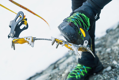 Close up of mountaineer removing crampon, Darran Mountains, Fiordland National Park, New Zealand