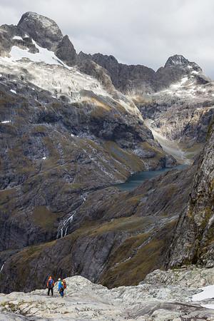 Two climbers descend towards Lake Turner, Darran Mountains, Fiordland National Park
