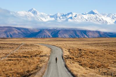 A male Te Araroa tramper road walking on Breamar Road with Southern Alps in background, Mackenzie Basin, Canterbury