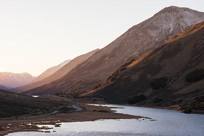 Evening light spills onto the hillsides surrounding Lake Ida, Inland Canterbury