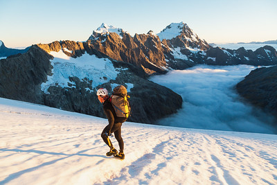 Mountaineer crosses snowfields below north face of Mount Patuki. Mount Waitiri, Mount Tutoko and Mount Madeline in background, Cleft Creek, Darran Mountains, Fiordland National Park, New Zealand