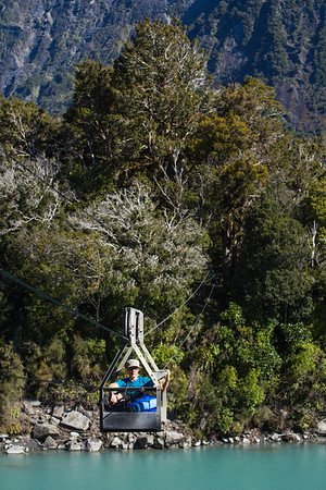 Female tramper on the cableway crossing over the Karangarua River, West Coast