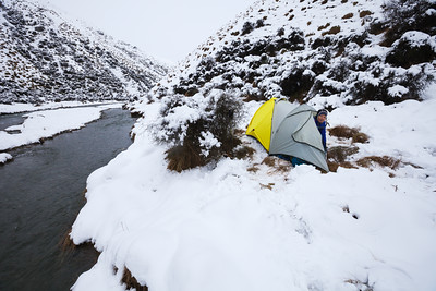 Female tramper looking out of tent door during stormy weather in the Arrow River, Motatapu Track, Otago