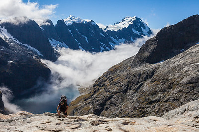 Climber above Lake Turner. Mounts Tutoko and Madeline in background, Darran Mountains, Fiordland National Park