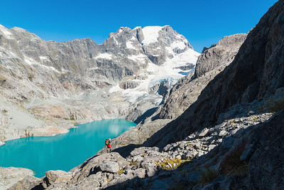 A mountaineer stands above Donne Glacier Lake and opposite Donne Face of Mount Tutoko, Darran Mountains, Fiordland National Park, New Zealand