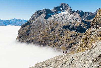 Two mountaineers standing on the slopes of Mount Tarewai, opposite Mount Te Wera, Lake Turner, Darran Mountains, Fiordland National Park, New Zealand