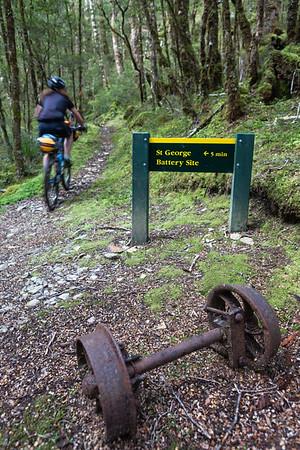 Bikepacker passes old tram bogies, Waiuta Track, Victoria Forest Park