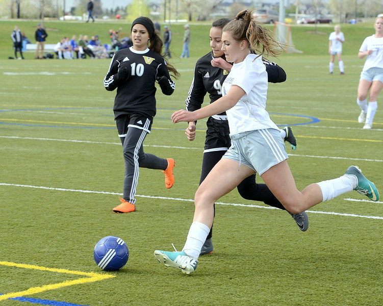 Resurrection Christian's Jadyn Hansen braces against the contact of Valley's Jensaint Perez to fire off the first goal of Thursday's match at Loveland Sports Park. (Mike Brohard/Loveland Reporter-Herald)