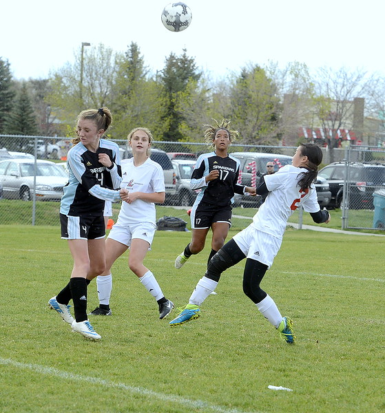 Loveland's Casey Bradley gets under her one-time attempt as Greeley West defender xxxx braces herself during Thursday's match at the Mountain View field. (Mike Brohard/Loveland Reporter-Herald)