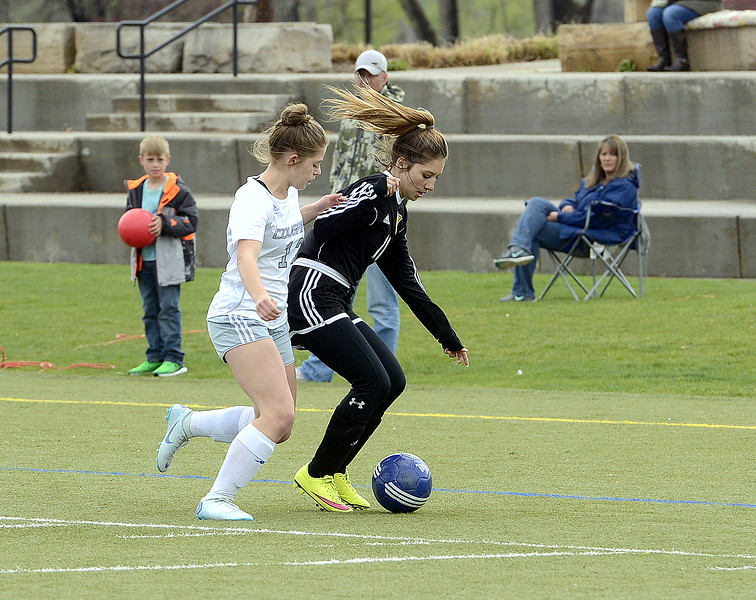Resurrection Christian's Colby Wolf battles with Valley's Tiffania Baker for possession of the ball during their match Thursday at Loveland Sports Park. (Mike Brohard/Loveland Reporter-Herald)