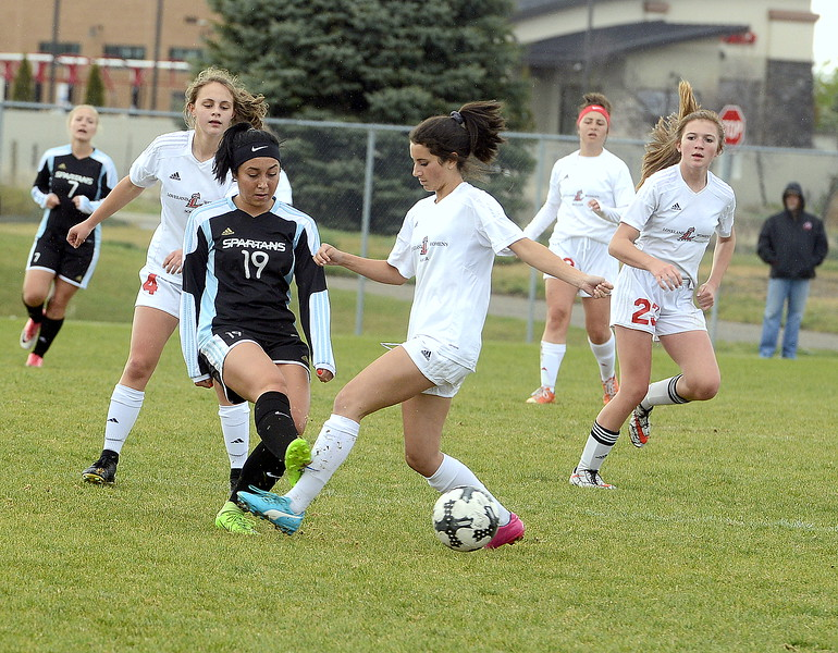 Loveland's Olivia Mascio takes a cleat the the shin as she battles for posession of the ball during Thursday's match with Greeley West at the Mountaiin View field. (Mike Brohard/Loveland Reporter-Herald)