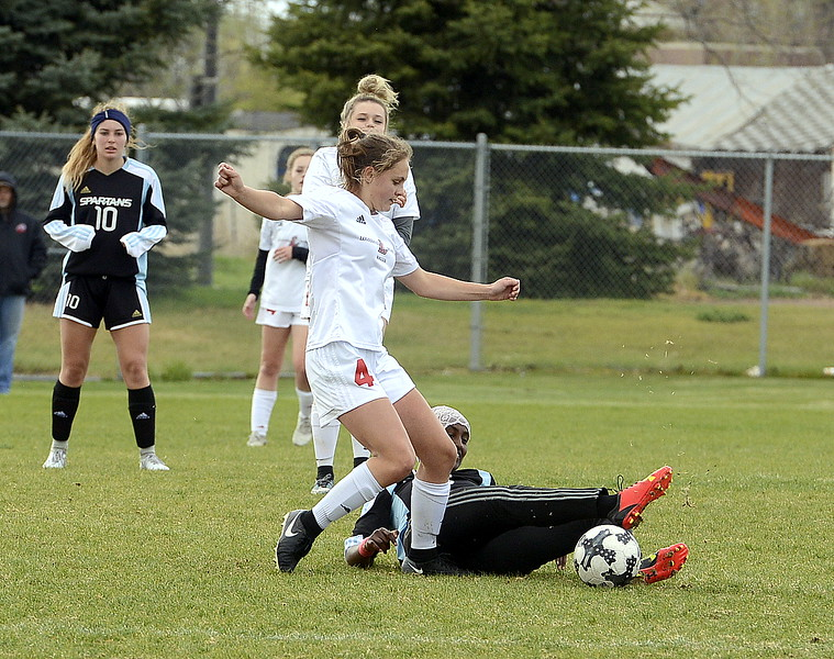 Loveland's Riley Hall moves in to get the ball as Greeley West's xxxxx slips on the Mountain View field turf during Thursday's match. (Mike Brohard/Loveland Reporter-Herald)