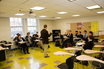 Mr. James Coviello, '99 in action, teaching a history class in Hogan Hall in early February. Note the cinder block along the base of the walls.