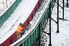 KELLY FLETCHER, REFORMER CORRESPONDENT -- Drew Christiansen shovels snow off the steps that run along the in-run of the Harris Hill ski jump
