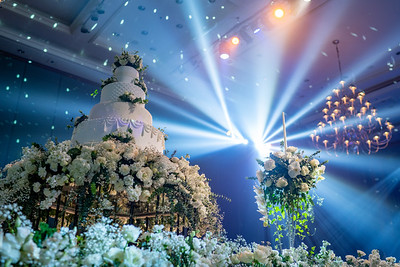Wedding cake on stage for the wedding reception ceremony and big lighting disco ball in ballroom.