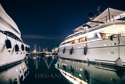 Luxury yachts in La Spezia harbor at night with reflection in water. Italy