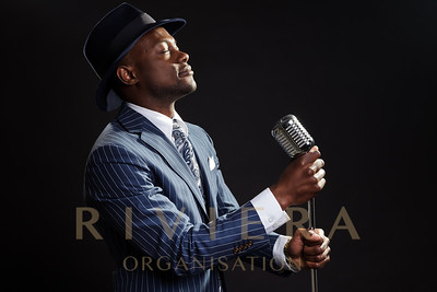 Black man with blue striped suit and hat singing. Jazz musician