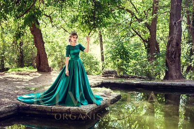 Young woman wearing a green dress explores a magical forest