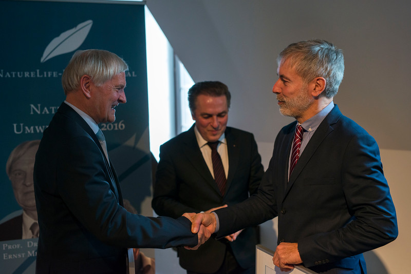 Astronaut Ernst Messerschmid and Christof Schenck shaking hands during the NatureLife-Umweltpreises 2016 ceremony (Senator e.h. Claus-Peter Hutter, President NatureLife-International in the background). Palais Livingston, Frankfurt, Germany. © Daniel Rosengren