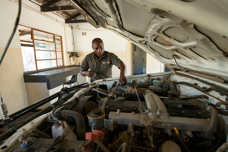 Fambi Tichaona (Workshop Manager) fixing a car in the workshop. Keeping the vehicles in good shape is crucial to be able to manage and protect the park. Gonarezhou National Park, Zimbabwe. © Daniel Rosengren / FZS