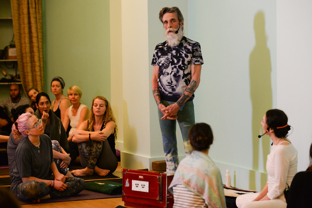David Life gives a dharma talk before teaching a yoga master class  with Sharon Gannon (looking on from bottom right corner of photo) at Jivamukti Yoga School in New York City. Photo by Derek Pashupa Goodwin.