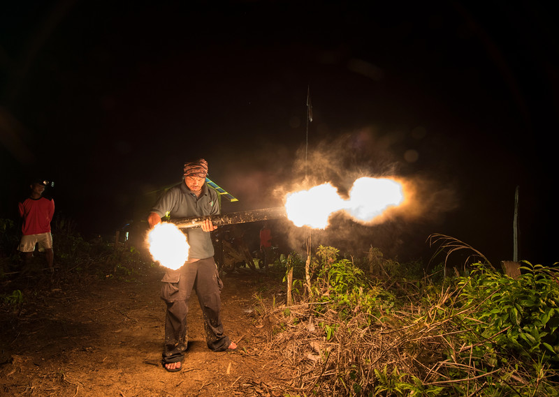 Mardani from the Wildlife Protection Unit demonstrating an elephant gun that makes a loud bang meant to scare of elephants from raiding crops and plantations. Near Bukit Tigapuluh, Sumatra, Indonesia. © Daniel Rosengren