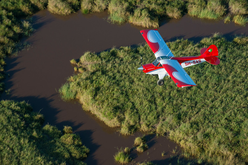 A Husky plane, donated by the German government, that will be used in anti-poaching patrolling and surveying the Serengeti. Here flown by Ramadhani Bakari Hamisi (TANAPA, Park Warden for the Control Room and soon to be Pilot). Serengeti NP, Tanzania. This is an aerial photo taken from another plane. © Daniel Rosengren