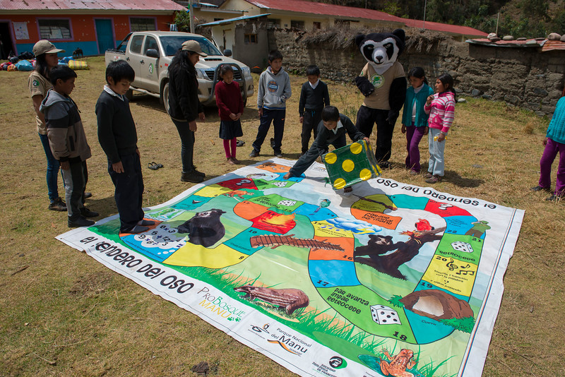 The Andean Bear mascot together with local children playing a game that teaches them about bears and the National Park. Patanmarca, Peru. © Daniel Rosengeren